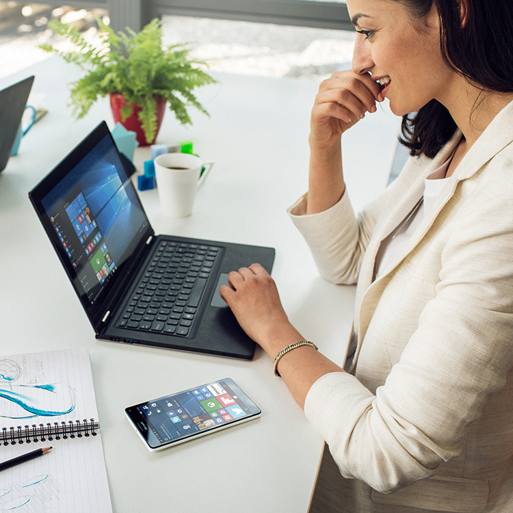 Woman sitting at a desk, working on laptop with a Lumia phone next to her on the desk