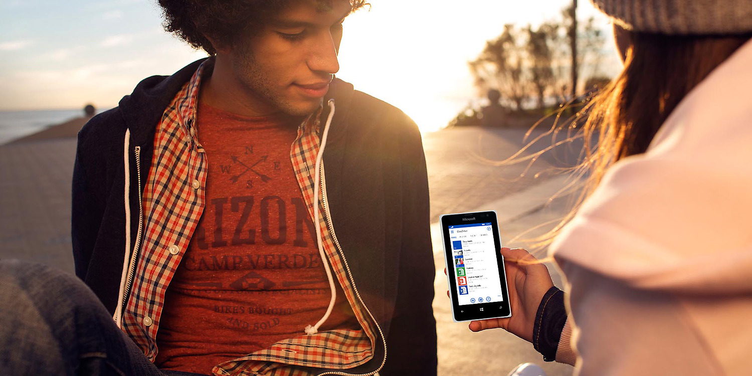 Young man and woman sitting on beach at sunset looking at white Lumia 435 girl is holding in her right hand