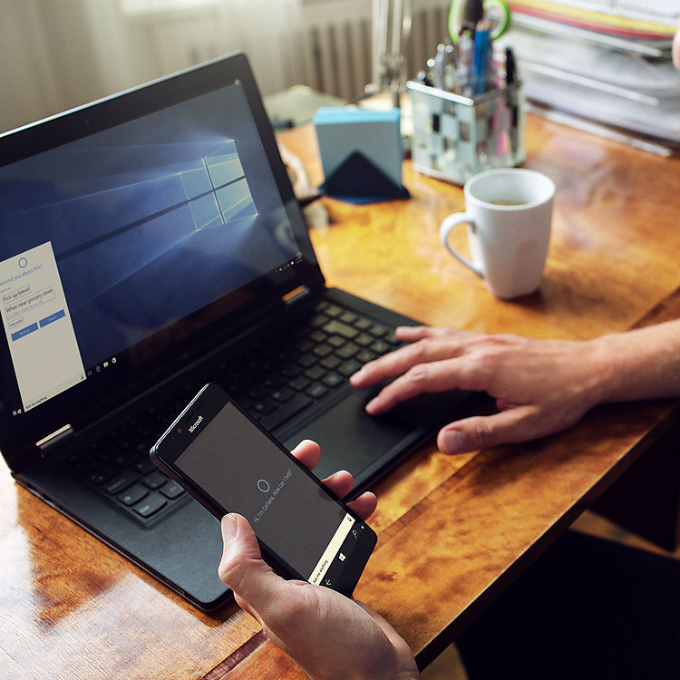 Man's hand holding Lumia phone in front of a desk at his laptop with both devices showing Cortana  on screen
