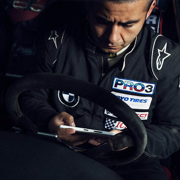 Man wearing racing overalls, sitting behind the wheel of a race car, looking at the screen of his Lumia phone