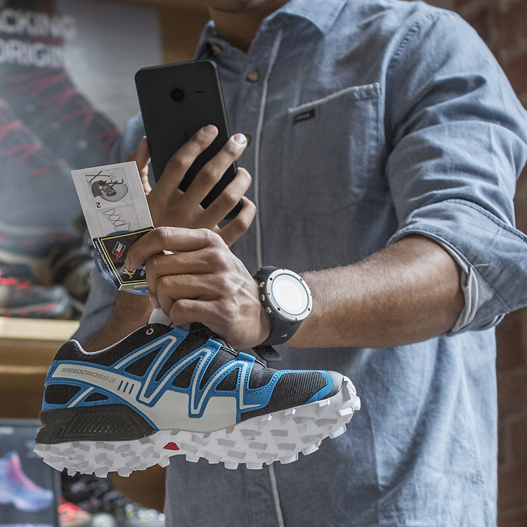Man taking picture of sneaker with sales tag attached with his Lumia phone