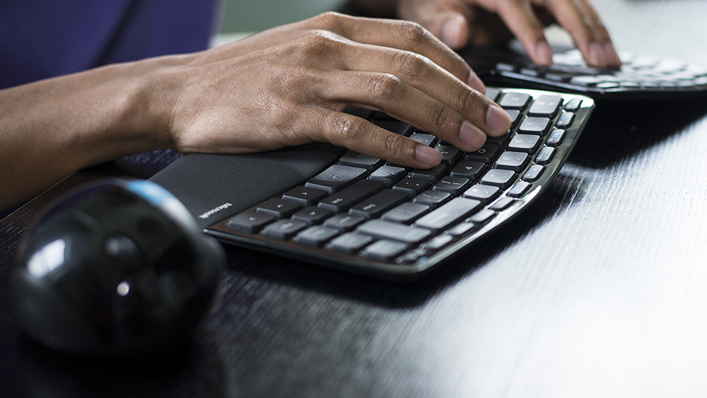 Hands typing on a Microsoft Scuplt Ergonomic keyboard