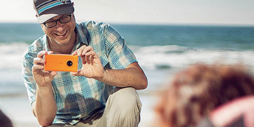 Man taking a photo of his family on a beach with an orange Lumia 830 phone