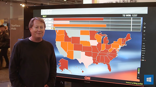 Video still of man in front of Microsoft Surface Hub