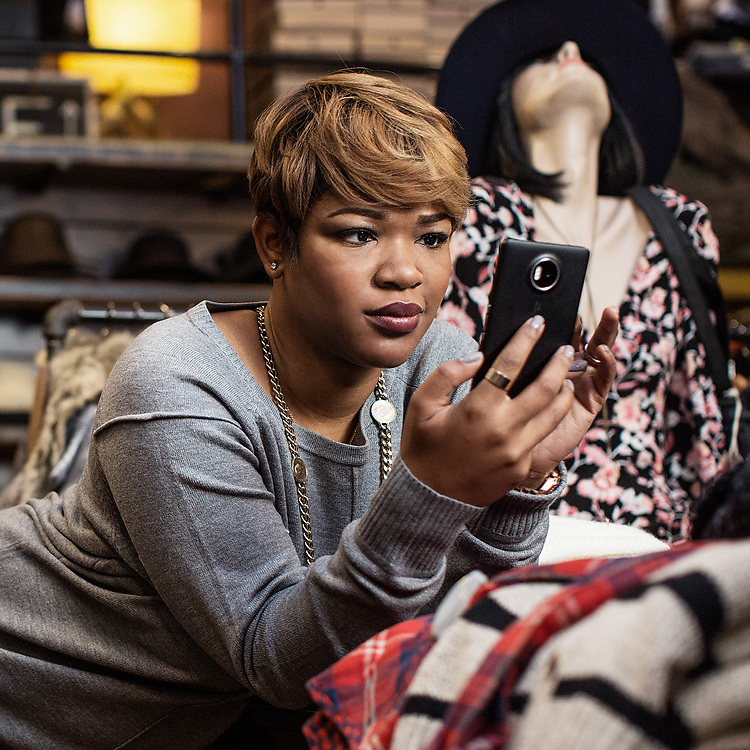 Woman in fashion boutique looking at her Lumia 950 XL