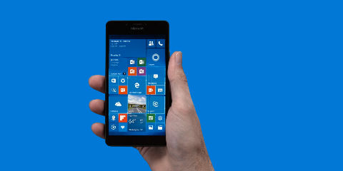 Man's hand holding Lumia 950 with start screen on blue background