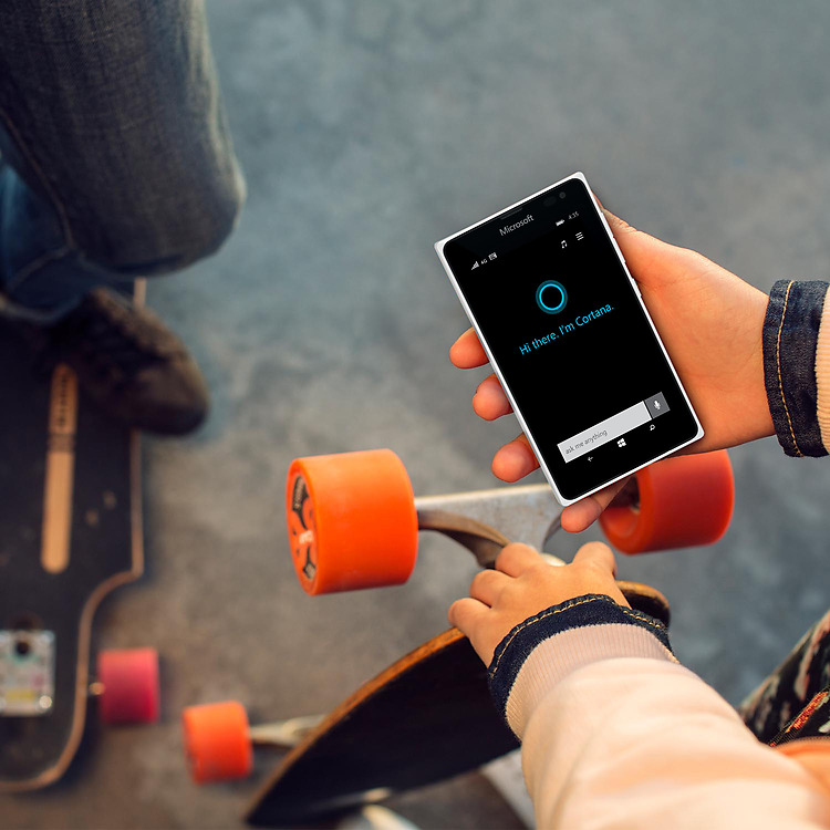 Young girl looking down white Lumia 435 in right hand with Cortana on screen while holding a skateboard upright with her left hand