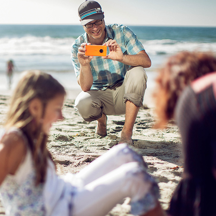 Man kneeling and using his Lumia phone to take a picture of wife and daughter on a beach