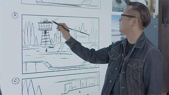 Man uses Pen on Surface Hub in real time two-way inking with his coworkers.
