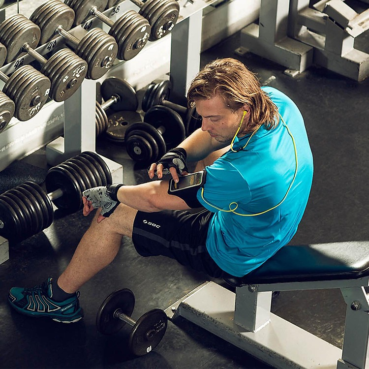 Man in gym clothes and wearing headphones sitting on weight bench tapping a Lumia phone strapped to his arm