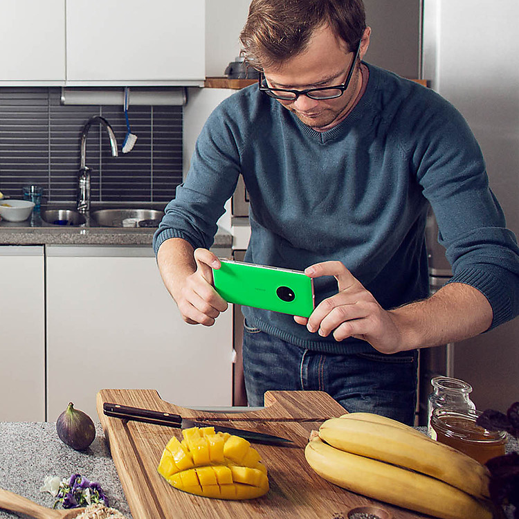 Man in kitchen taking a photo of a diced mango on a cutting board and other with his Lumia phone
