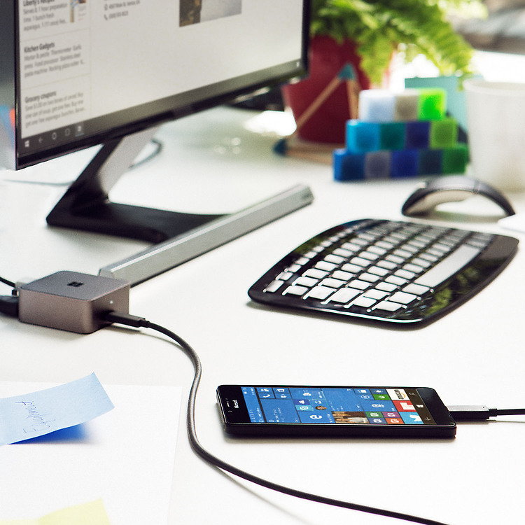 Lumia 950 XL phone on desk plugged into monitor through Microsoft Display Dock next a keyboard