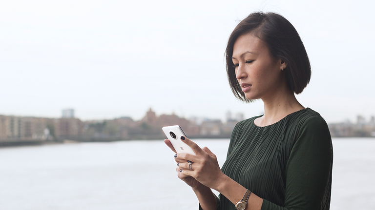 Woman holding and looking at white Lumia phone with a river and city in the background
