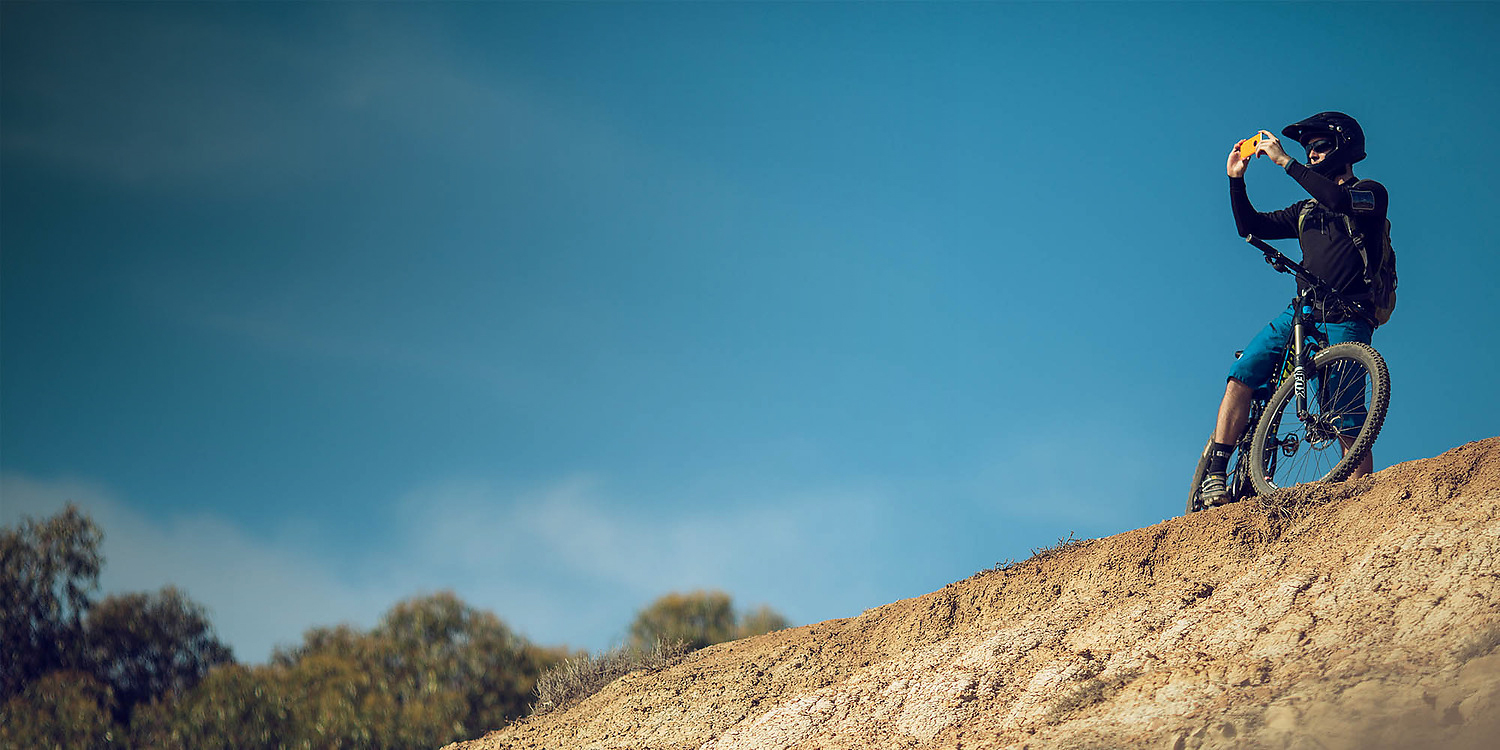 Male mountainbiker taking picture with Lumia 830 on a ledge with a blue sky behind him
