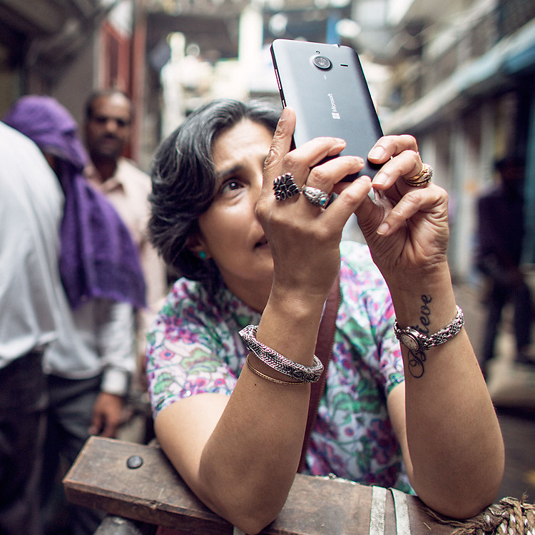 Elderly woman taking a photo with her Lumia phone while standing in a bazaar