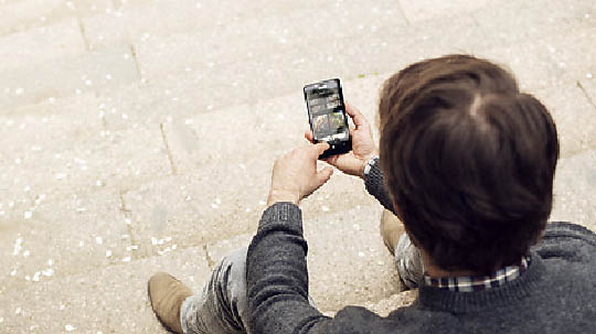 Man sitting on steps looking at photo gallery on his Lumia 950