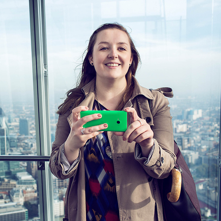 Woman holding Lumia phone and smiling into camera with a city landscapebelow her in the background