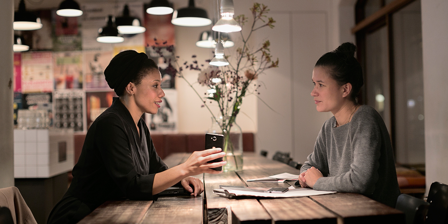 Two women talking over a dark lit table with the woman on the right showing her Lumia phone to the woman across the table.