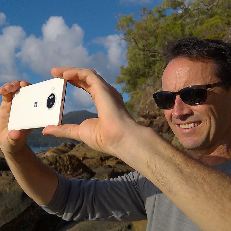 Man wearing sunglasses taking a photograph with his Lumia 950 XL