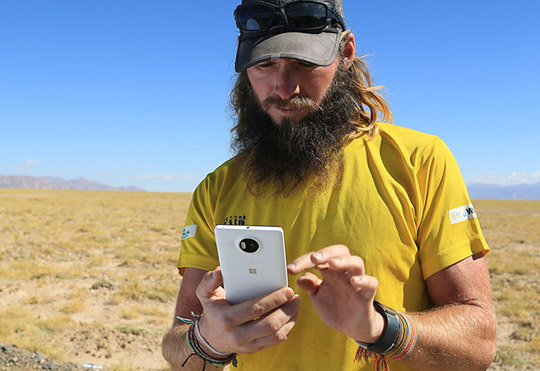 Bearded man wearing cap with sunglasses on it looks at his Lumia 950 XL phone with a desert landscape and mountain range behind him