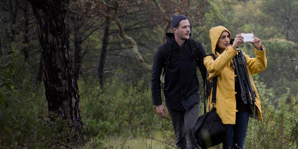 Een vrouw en een man in regenkleding die door een regenachtig bos lopen; de vrouw draagt camera-uitrusting bij zich en maakt een foto met haar witte Lumia 950.