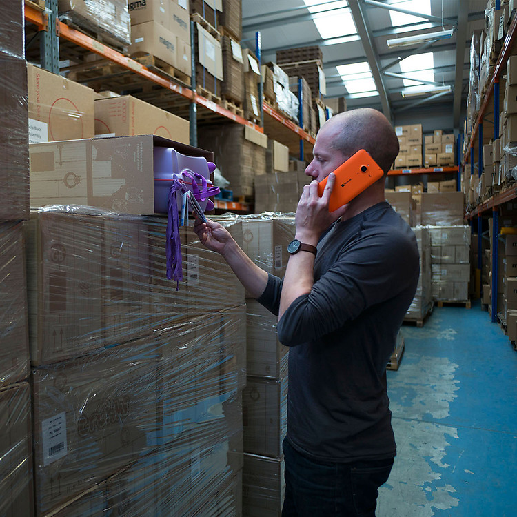 Man talking on orange Lumia phone in warehouse, while inspecting a Trunki product in a box