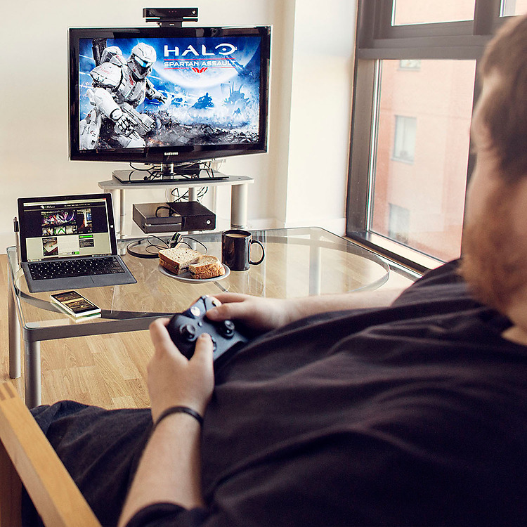Man playing Halo on his Xbox with a Surface Pro 4 and a Lumia phone on the coffee table in front of him