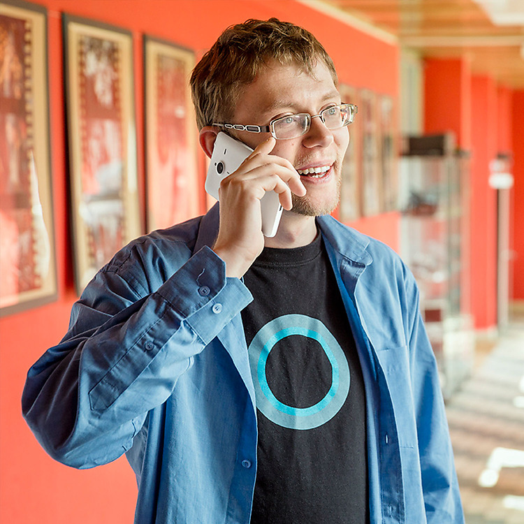 Man wearing tshirt with Cortana logo talking on a Lumia phone while standing in hallway with red walls