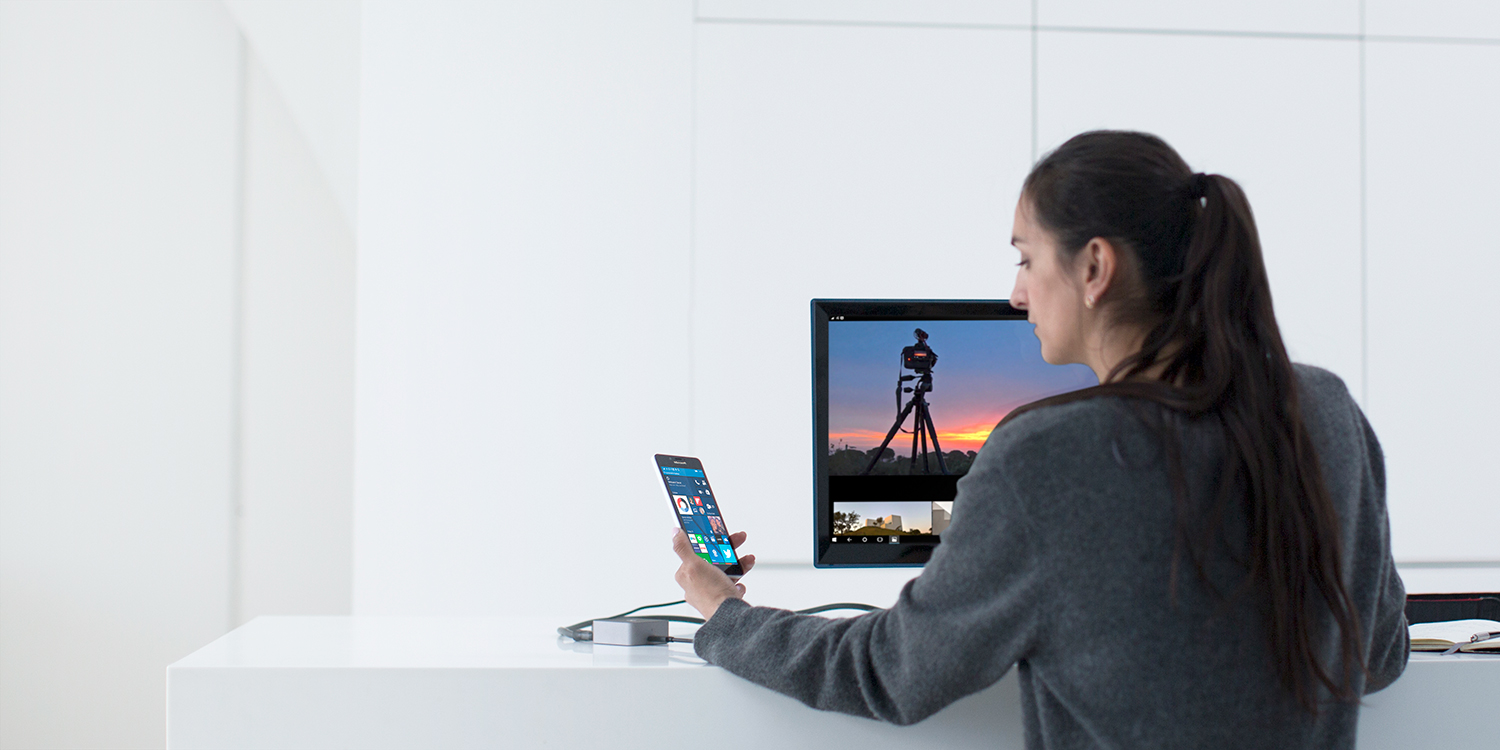 Woman sitting at desk, looking at her Lumia phone with Windows 10 start screen