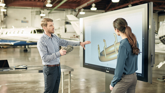 Man using touchscreen on Microsoft Surface Hub and woman watching