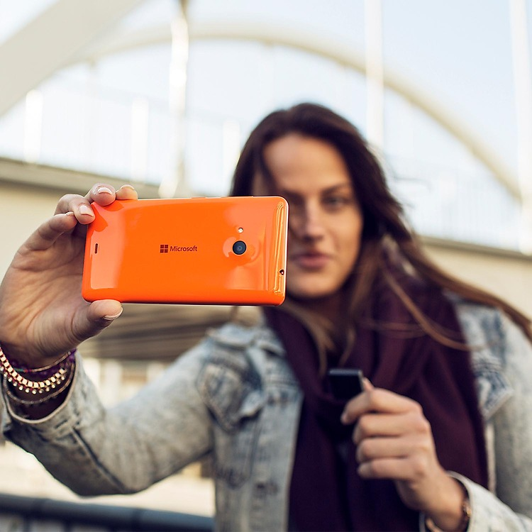 Woman taking a selfie with an orange Lumia phone holding a Treasure Tag in other hand