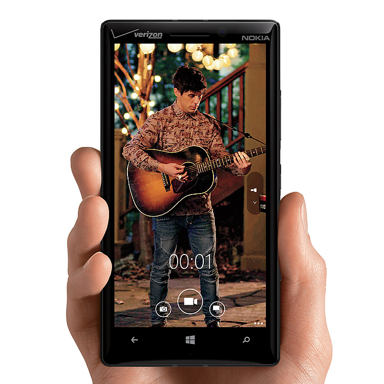 Man's hand holding Lumia icon with video playback screen of a man playing guitar