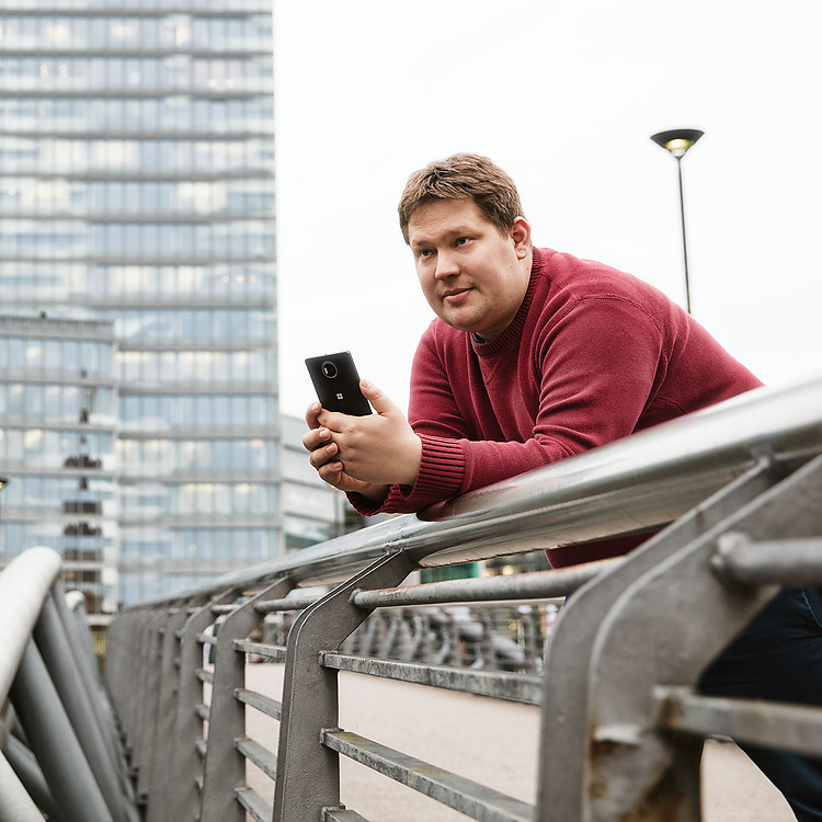 Man leaning over bridge holding a black Lumia 950 XL with a skyscraper in the background