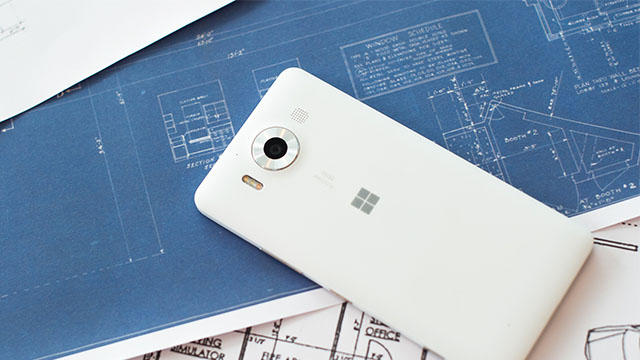 A white Lumia 950 display side down on top of blueprints on desk