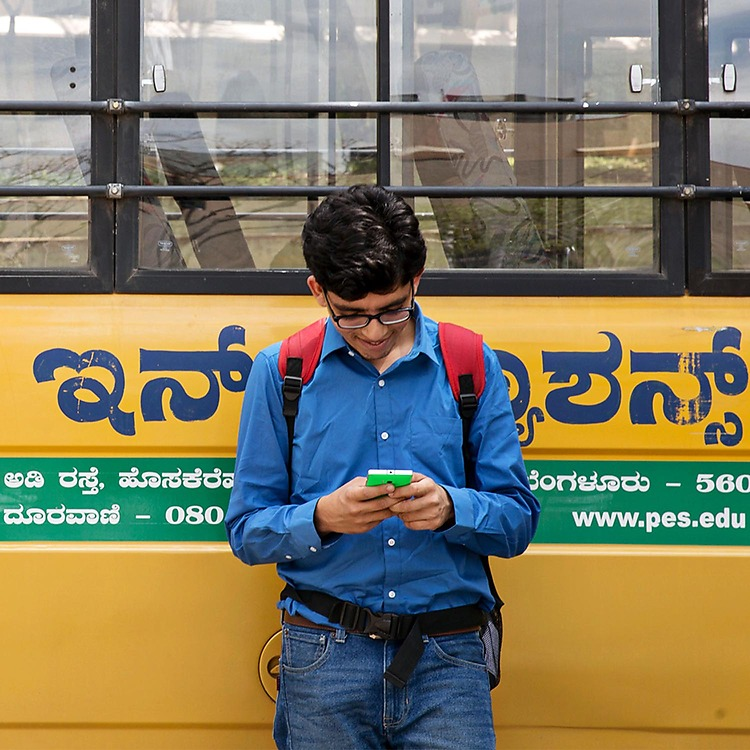 Young man wearing a backpack while leaning against the side of a bus and texting on his Lumia phone