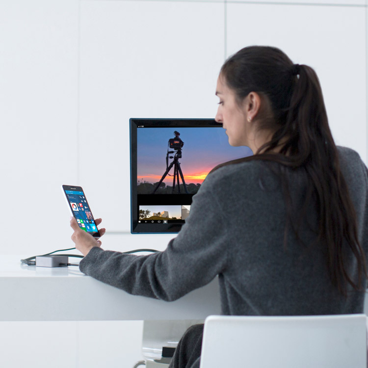 Woman sitting at desk with camera and monitor, looking at her Lumia 950