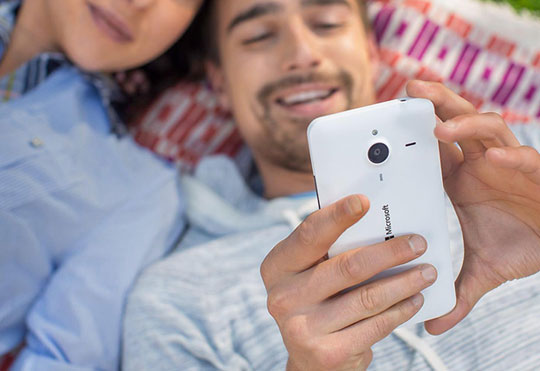 Man and woman lying next to each other on a picnic blanket looking at the Lumia 640 XL in the man's hand