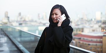 Woman talking into white Lumia phone while standing on a roof terrace with a city in the background