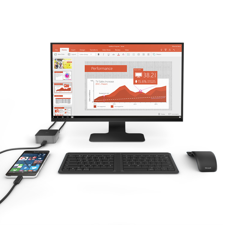 Lumia phone on desk plugged into a Microsoft Display Dock with keyboard, monitor and mouse next to it