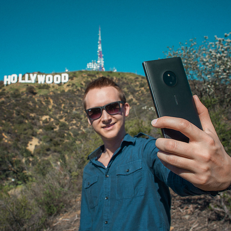 Young man wearing sunglasses taking a selfie with the Hollywood sign in the background