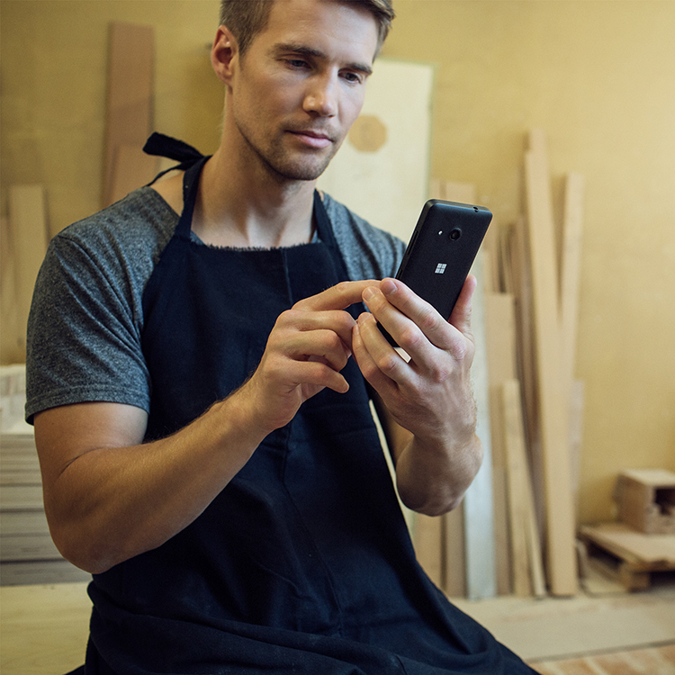 Man tapping the screen of his Lumia 550 while wearing a work apron in his workshop