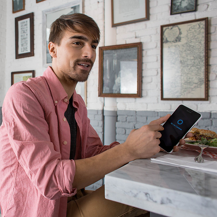 Man pointing to the Cortana screen on his Lumia 640 XL in a cafe