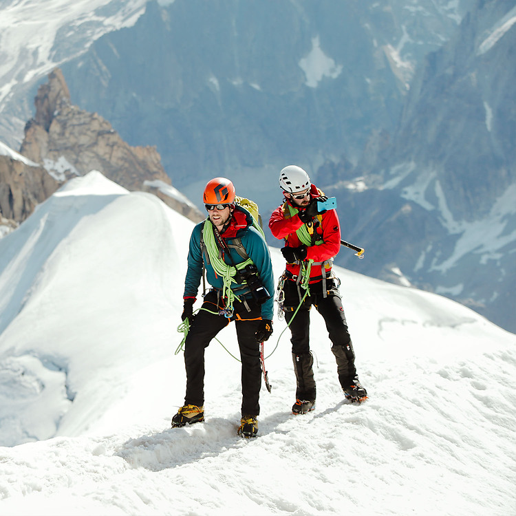 Two moutain climbers standing on a moutain peak, taking a picture on their Lumia phone with other moutain peaks behind them