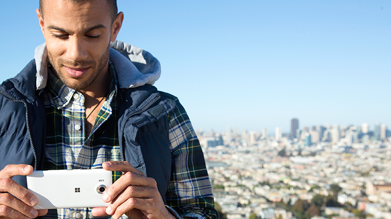 Man standing outside, smiling while taking a picture with his Lumia with a sprawling city in the background